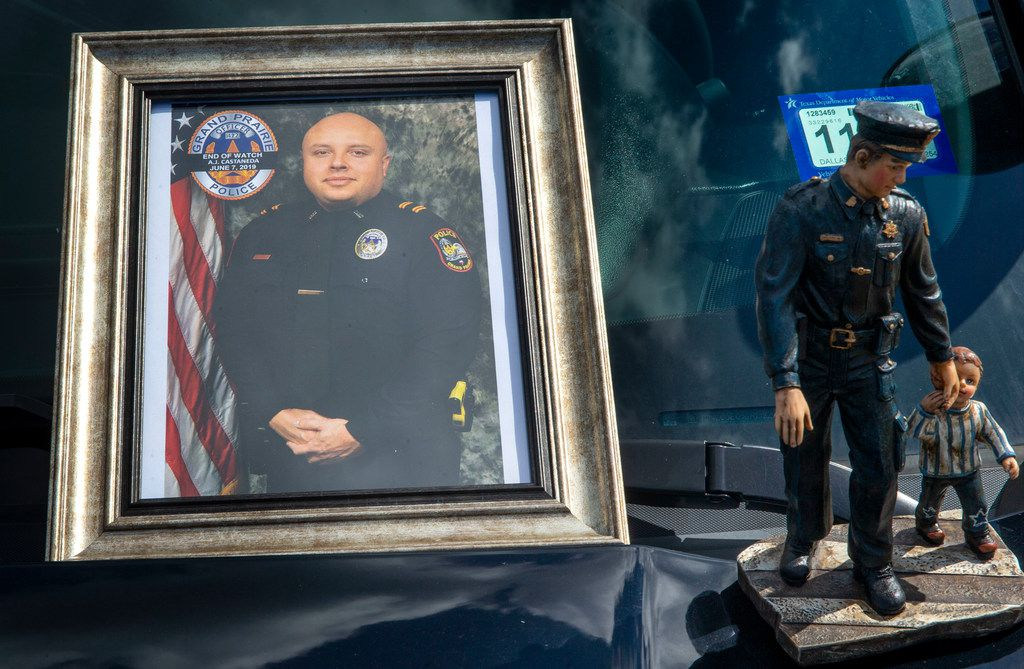 """A photograph of Grand Prairie Police Officer Albert """"A.J."""" Castaneda and a statue adorn the hood of a police vehicle at the Grand Prairie Police Department in Grand Prairie, TX, on Friday, June 7, 2019. Castaneda was struck and killed by a vehicle as he ran traffic enforcement Friday morning. (Lynda M. Gonzalez/The Dallas Morning News)"""