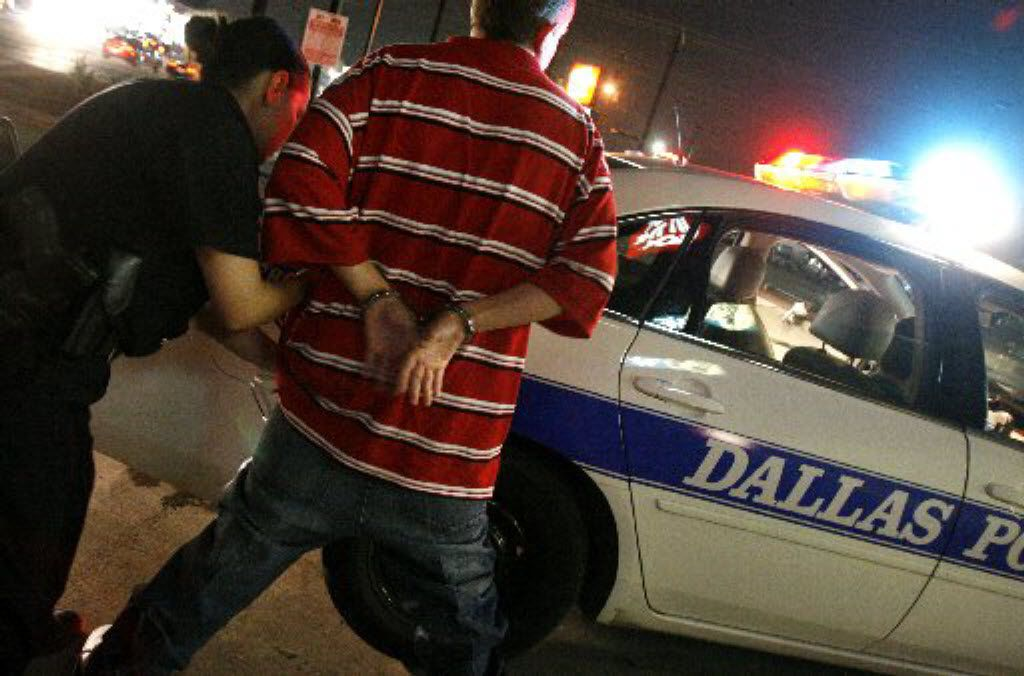 A Dallas police officer searches a juvenile who violated curfew.