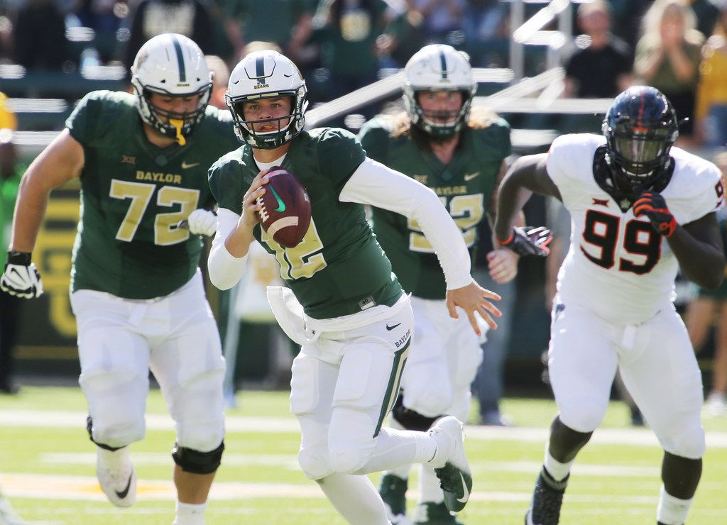 Baylor quarterback Charlie Brewer, center, runs past Oklahoma State's defensive tackle Trey Carter, right, during an NCAA college football game, Saturday, Nov. 3, 2018, in Waco, Texas. (Rod Aydelotte/Waco Tribune-Herald via AP)