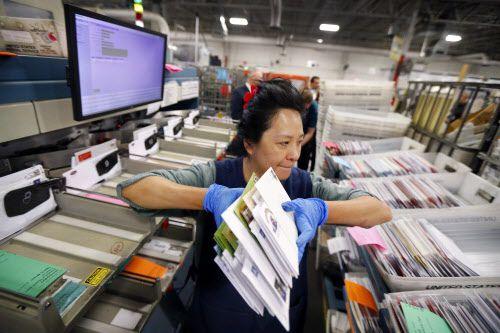 Petty Chow maneja envios cancelados en una bodega de almacenamiento de correo en Coppell. TOM FOX/DMN