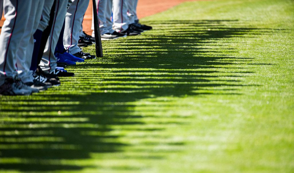 FILE - Rangers players' shadows appear on the grass as they line up for the national anthem before a spring training game against Kansas City on Sunday, Feb. 26, 2017, in Surprise, Ariz. (Ashley Landis/The Dallas Morning News)