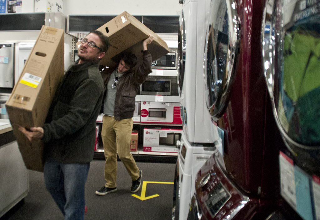 Jeremy Nye, left, and Ethan Nye stand in line to purchase televisions during the 5 p.m. opening of Black Friday deals at Best Buy in Jackson, Mich., Thursday, Nov. 26, 2015.