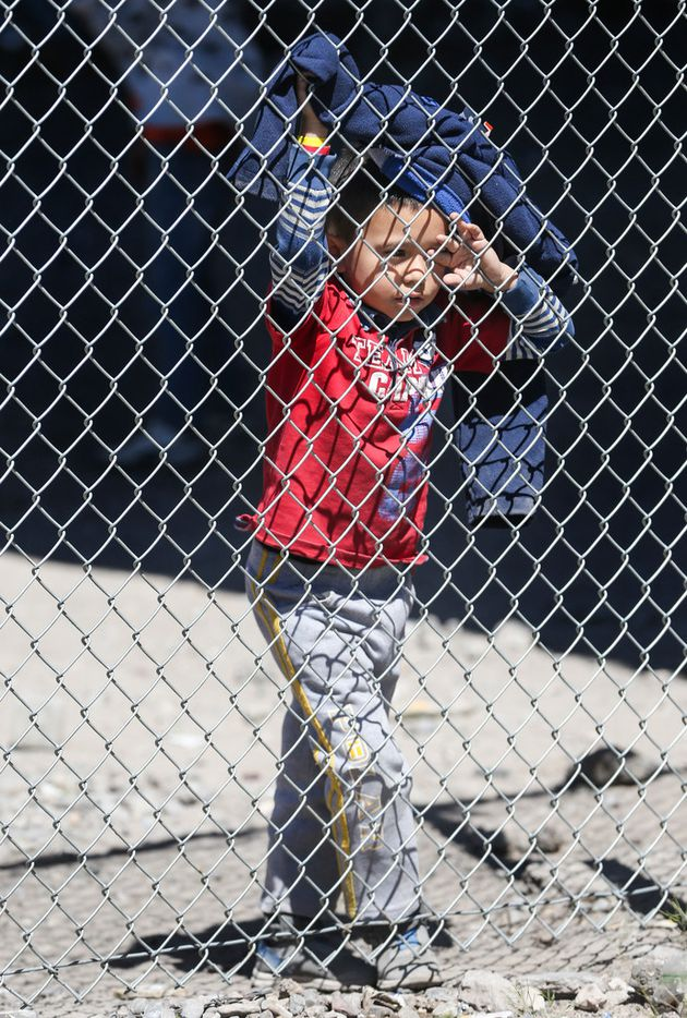 A child wiped dust from his eyes as the wind whips in a temporary transition area where migrants seeking asylum are held under the Paso Del Norte bridge in El Paso on March 29, 2019.