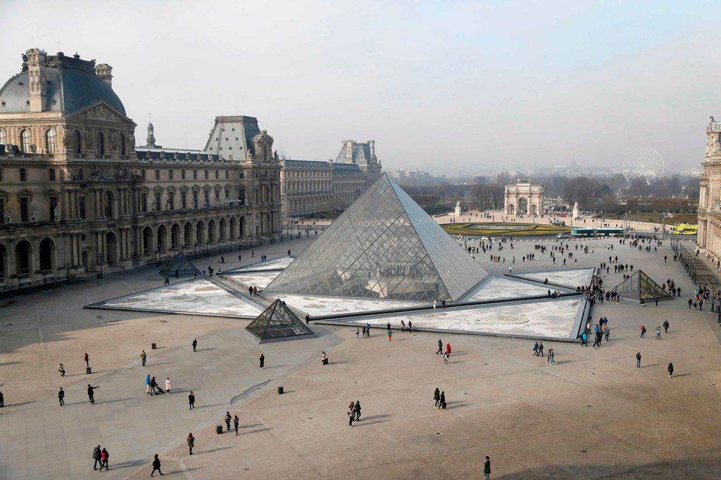 People walk around the pyramid of the Louvre, designed by Chinese-American architect I.M. Pei, outside the Louvre museum in Paris.