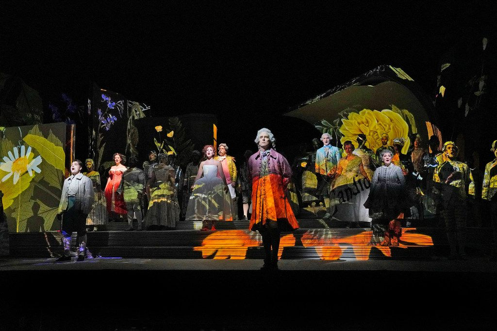 The cast of Santa Fe Opera's Candide performs onstage with projections by 59 Production.  (Photo by Ken Howard)