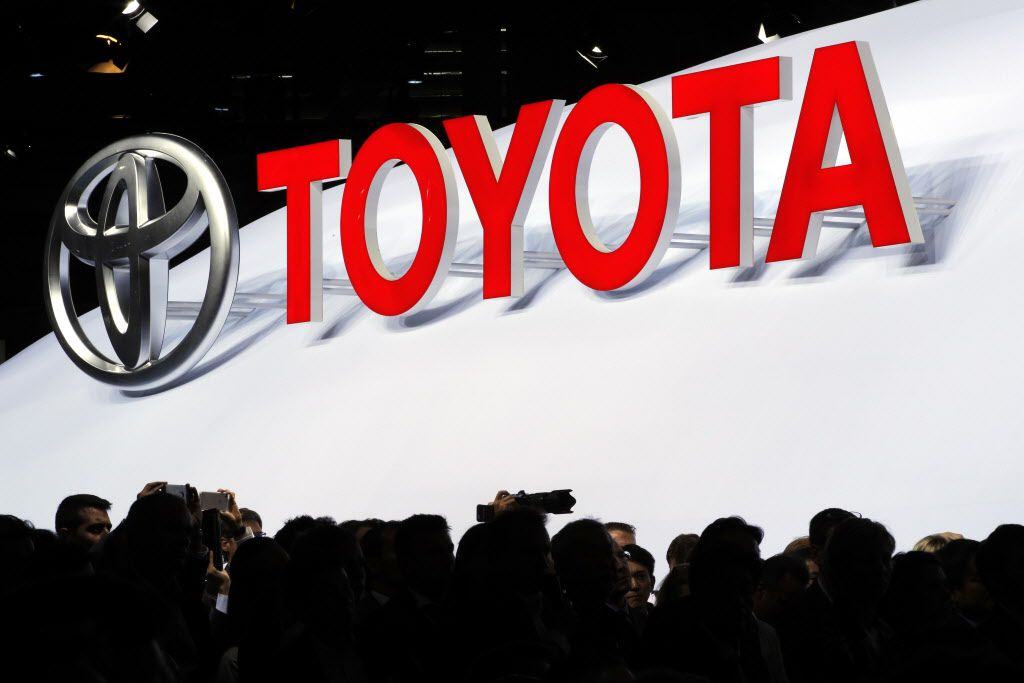 FILE - In a Thursday, Sept. 29, 2016 file photo, the logo of Japanese car manufacturer Toyota is displayed behind members of the media Toyota at the Paris Auto Show in Paris, France. Toyota will test a new car-sharing system next year that lets users unlock doors and start cars with their smartphones. The Smart Key Box system eliminates the need for a physical key. Toyota will test the system in San Francisco with the Getaround car-sharing service starting in January 2017. (AP Photo/Christophe Ena, File)
