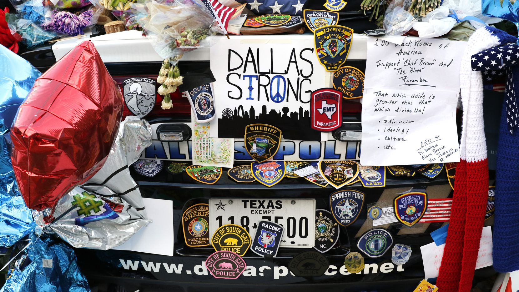 Two Dallas police patrol cars were covered with notes, flowers, balloons and other items as part of a makeshift memorial at the Jack Evans Police Headquarters on July 14. Patches from police departments from across the country are part of the memorial. Five police officers were killed and many others injured in an ambush on July 7 during a march against recent police involved shootings.