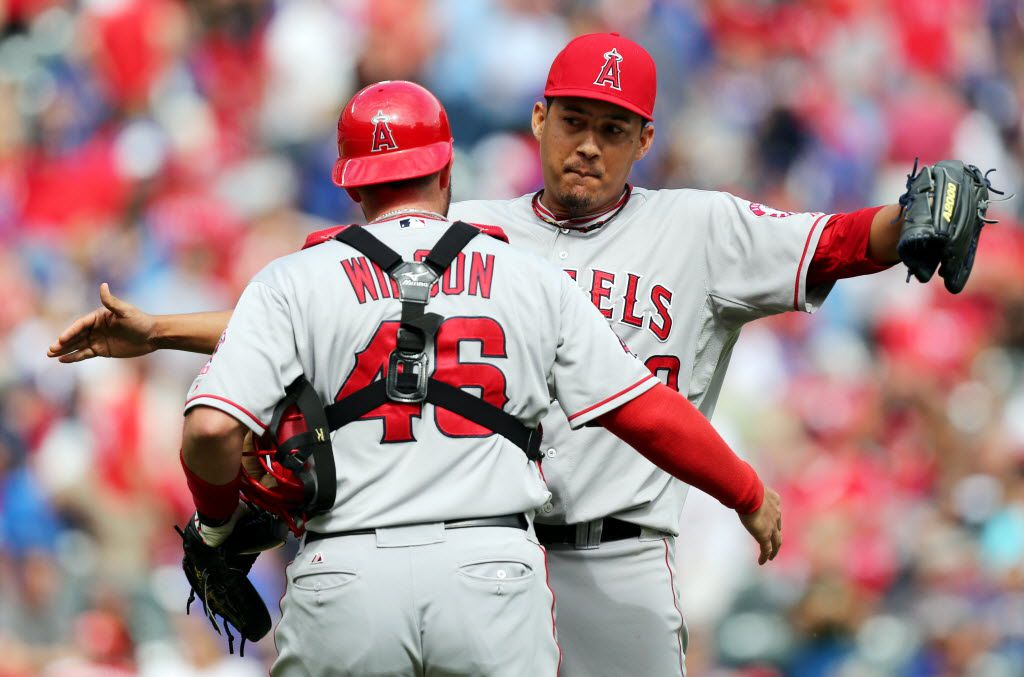 Angels' closer Ernesto Frieri (49) is congratulated by catcher Bobby Wilson (46) after getting the final out in Los Angeles' 5-4 win during the Los Angeles Angels vs. the Texas Rangers major league baseball game at Rangers Ballpark in Arlington on Sunday, September 30, 2012. (Louis DeLuca/The Dallas Morning News)