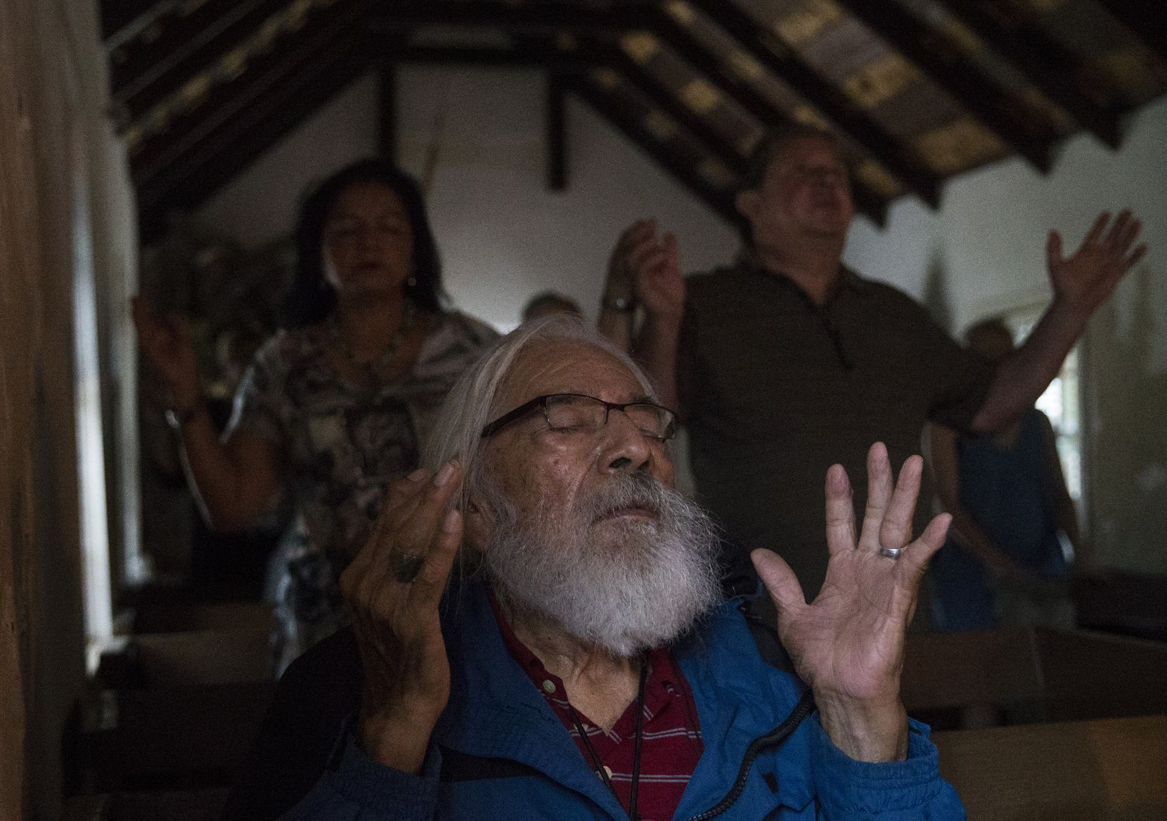 """Jose Ramirez, a longtime attendee of Mass at La Lomita, holds up his hands in prayer during a sunrise Mass at the chapel near Mission, Texas. """"I've been coming here as long as, well, I guess when they were attacking Pearl Harbor,"""" Ramirez said. """"I hope they don't build a wall around this place. It means so much to so many people."""""""