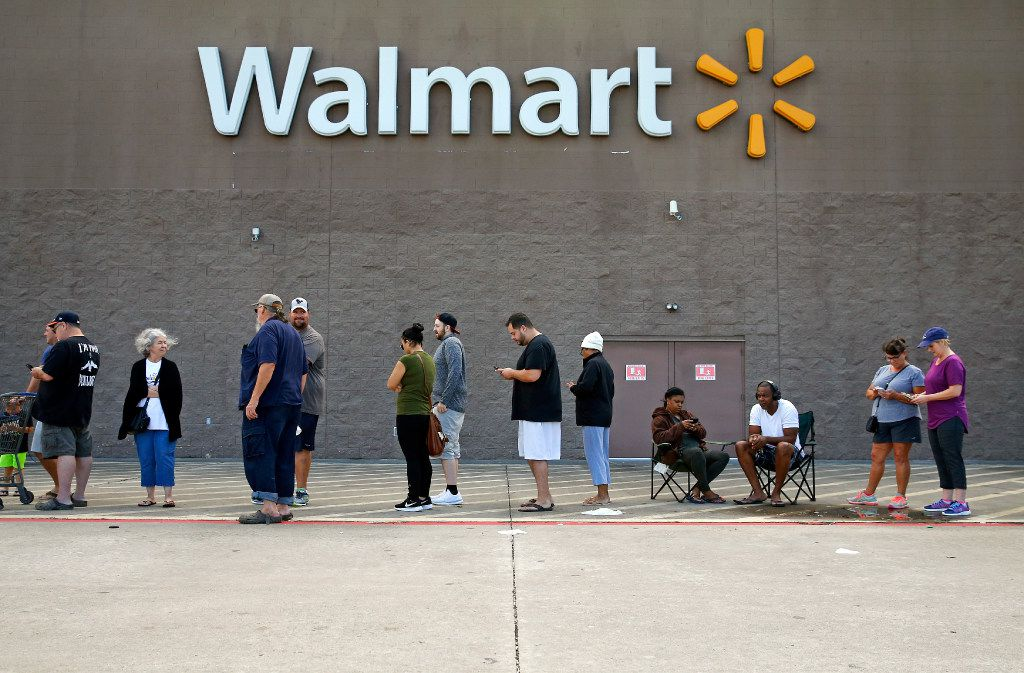 A line stretches across the front of the Wal-Mart in Pearland on Wednesday as people wait for the store to open. It's the first time the store has opened since Hurricane Harvey. Hundreds waited to get food and supplies.