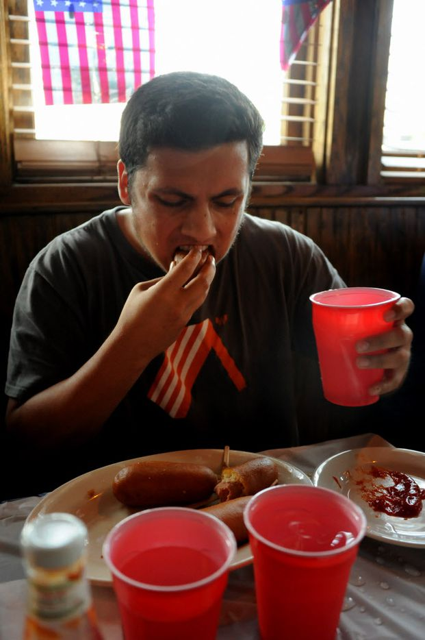Jordan Desilva eats corn dogs at the 7th annual Brass Knuckles Corn Dog Beatdown at The Libertine Bar on July 4, 2015.