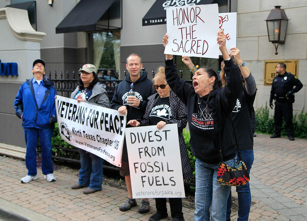 """Arin Maupin (right) of Fort Worth holds a sign that reads """"Honor the Sacred"""" at a protest outside an Energy Transfer Partners meeting at the Hilton Hotel/Park Cities in Dallas."""