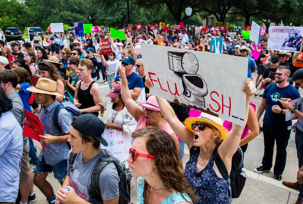 A protester held up a sign while chanting during a One Texas Resistance rally on the south steps of the Capitol on the first day of a legislative special session July 18, 2017. She was among those opposing the bathroom bill.