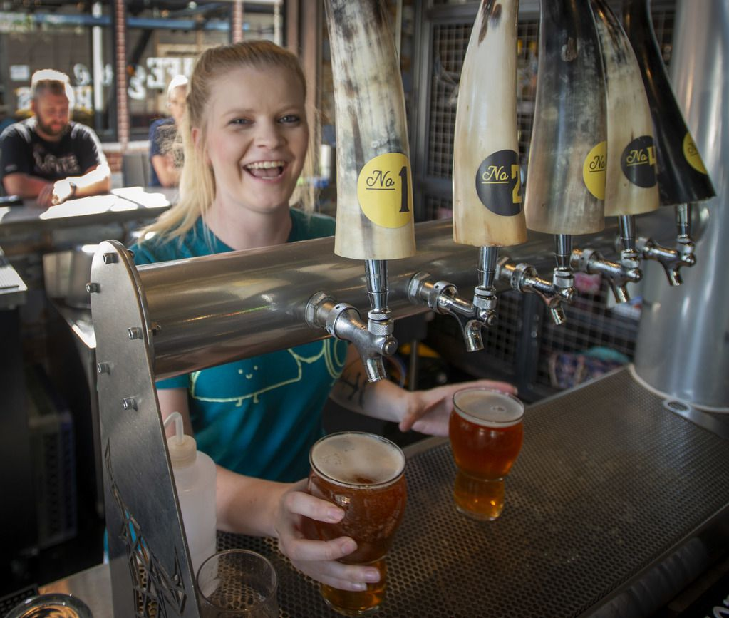Bartender Lauryn Henderson serves beer with a smile at By the Horns Brewing.