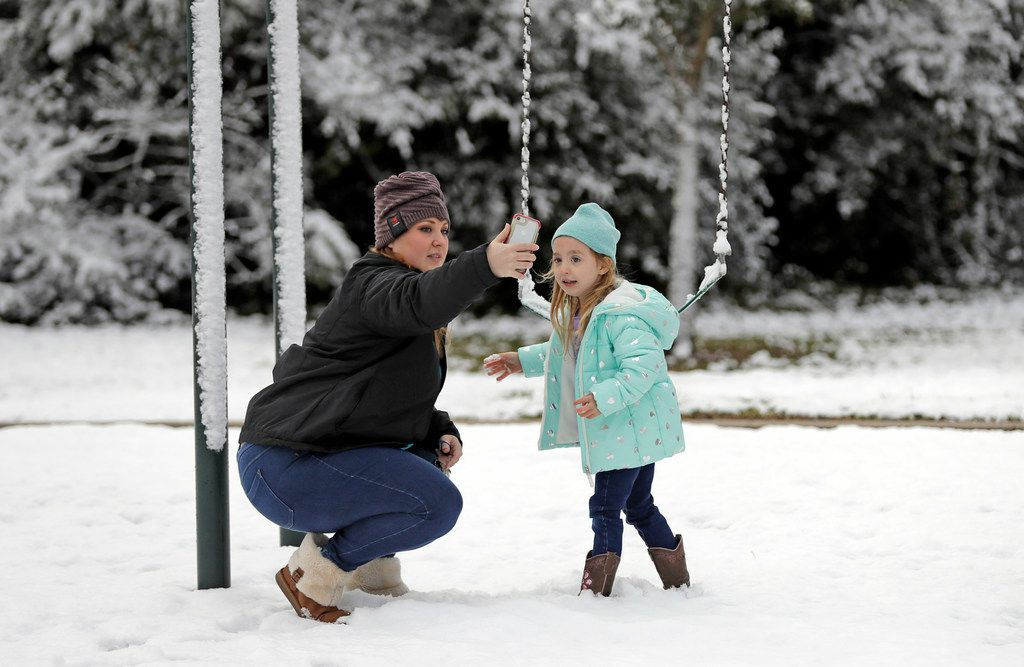 Cat Davis, left, takes a picture with her daughter, Lilly, 4, while playing in the snow at Meyer Park Friday, Dec. 8, 2017, in Spring, Texas, north of Houston. It was the first time Lilly has seen snow. Rare snowfall in many parts of southern Texas has knocked out power to thousands, caused numerous accidents along slick roadways and closed schools. The weather band brought snow to San Antonio, Corpus Christi, Houston and elsewhere.