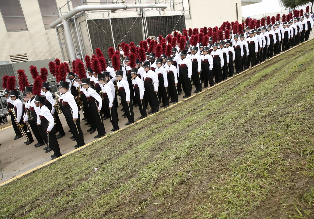The Red Oak Mighty Hawk Band waited next to freshly mowed, muddy grass before performing in the UIL competition at John Kincaide Stadium on Thursday.