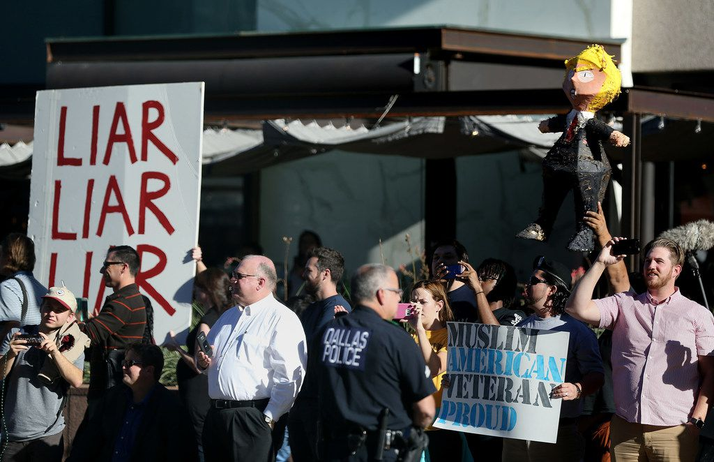 Protesters along Ross Avenue as viewed from the motorcade of President Donald Trump as he visits the Belo mansion for an event in downtown Dallas Wednesday October 25, 2017. President Trump participated in a hurricane recovery briefing, a Republican National Committee roundtable and gave remarks at a reception. (Andy Jacobsohn/The Dallas Morning News)