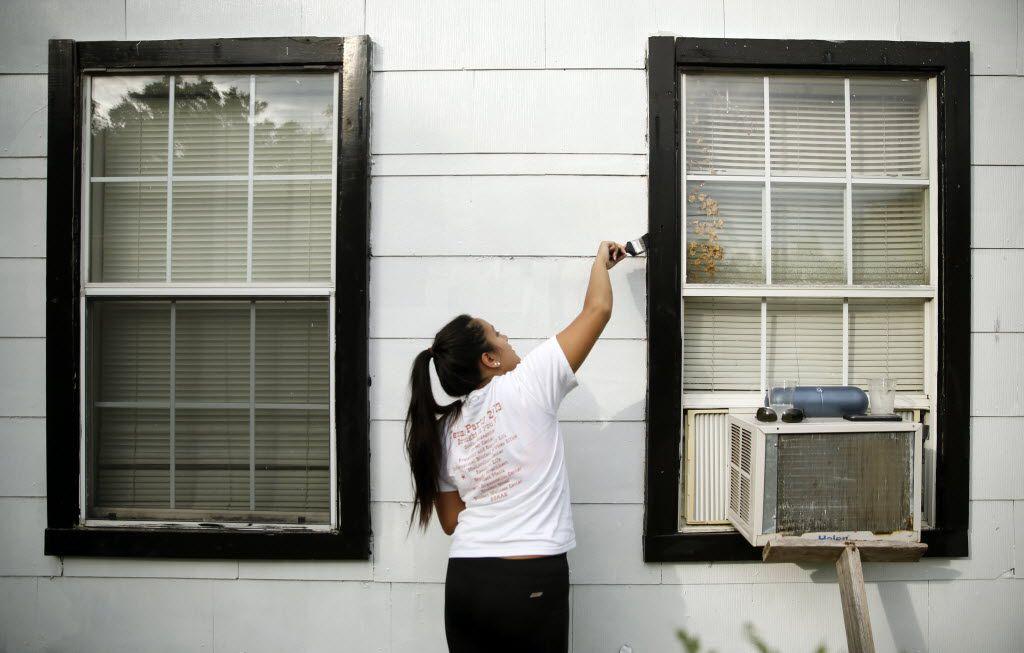 Data editor Megan Sotelo paints the trim on Rosie Glespie's home.