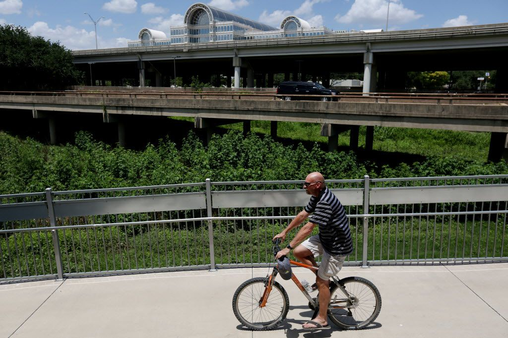 A cyclist rides west along the Trinity Strand Trail's eastern terminus with Interstate 35, near Oak Lawn Ave. in the Design District neighborhood east of I-35E (elevated, background) as the Infomart is seen in the background across the highway in Dallas Tuesday June 22, 2016.