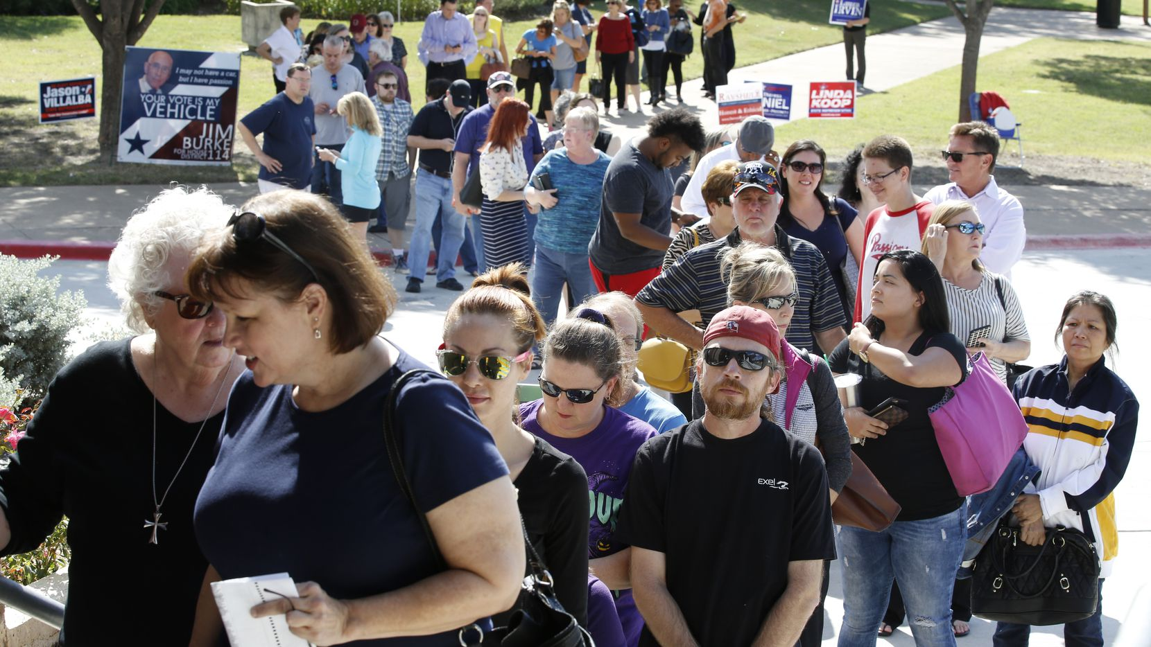 People wait in line to vote at Fretz Park Dallas Public Library in Dallas on Monday, October 24, 2016 on the first day of the early voting period in Texas.