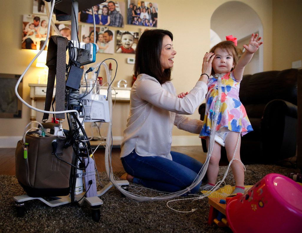 Christina Gregory, 2, has to wear a diaphragmatic pace maker in a backpack to keep her breathing on track as well as a ventilator unit (left) that hooks up to a trachea tube in her neck to assist in breathing,  Tuesday, January 31, 2017.  Mother Natalie Gregory has 24-hour medical care for her 2 year-old daughter who suffers from CCHS (Congenital Central Hypoventilation Syndrome), a genetic disorder that affects her breathing. Two pediatric nurses keep a watchful eye on Christina at their Southlake,Texas home. The Gregorys are affected by Texas' change to their Medicare healthcare coverage, switching to a MCO plan from an HMO plan, limiting their care to within the region -a cumbersome issue for families dealing with 24/7 care.