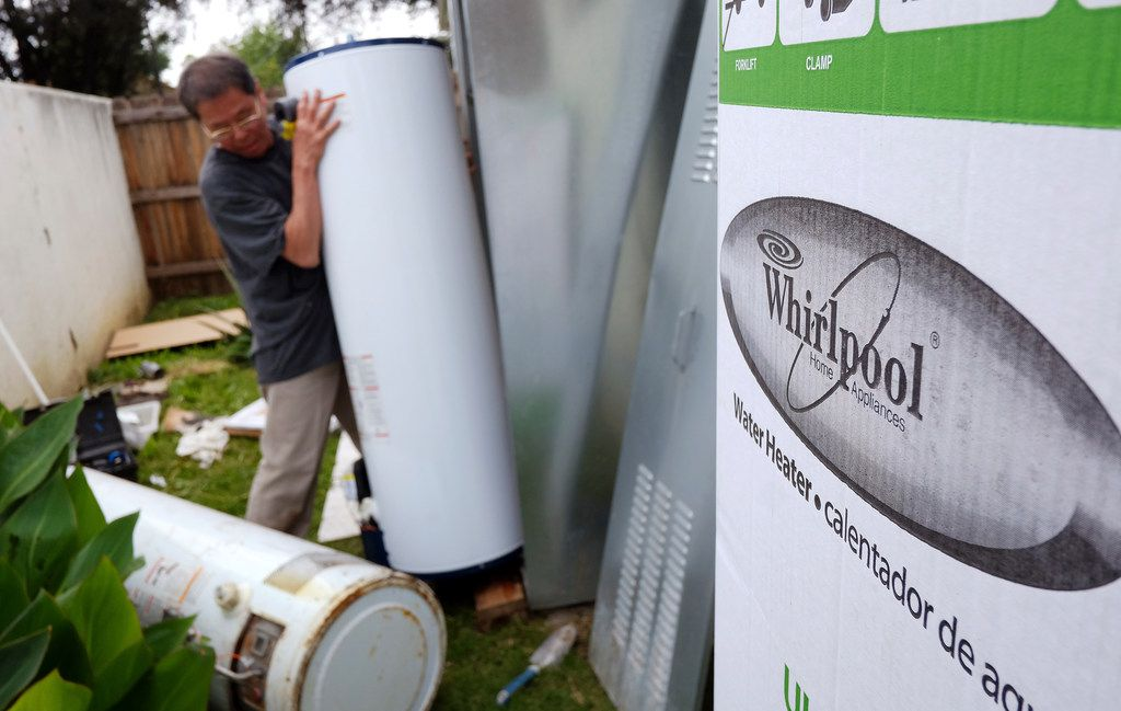A repairman installs a Whirlpool water heater at a home in Los Angeles.