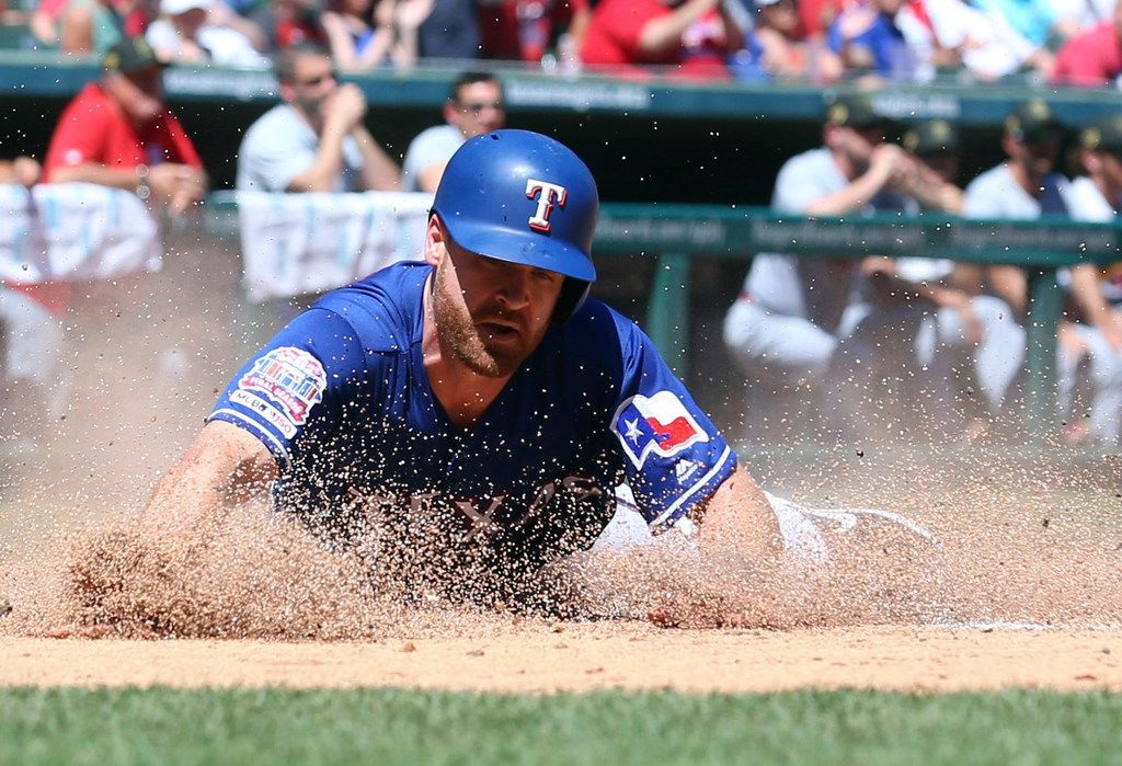 Texas Rangers Logan Forsythe (41) slides home to score on a double by Texas Rangers right fielder Hunter Pence (24) in the fourth inning of a baseball game against the St. Louis Cardinals Sunday, May 19, 2019 in Arlington, Texas. (AP Photo/ Richard W. Rodriguez)