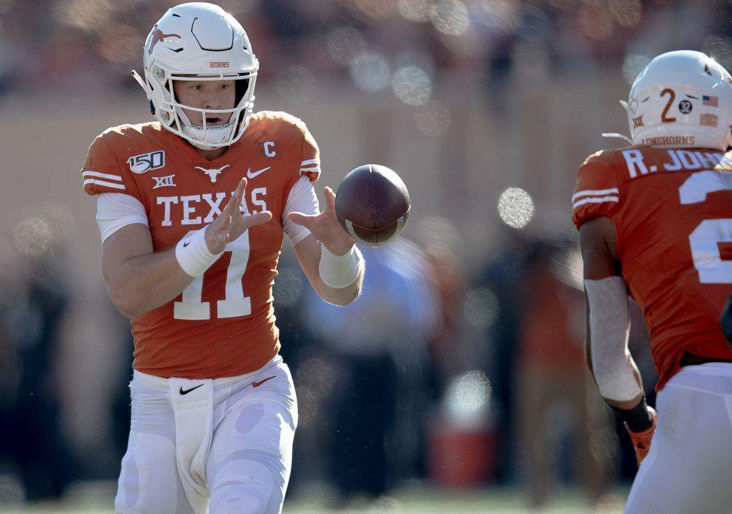 Texas quarterback Sam Ehlinger (11) receives a flea flicker from running back Roschon Johnson (2) during an NCAA college football game against Kansas State, Saturday, Nov. 9, 2019, in Austin, Texas. (Nick Wagner/Austin American-Statesman via AP)