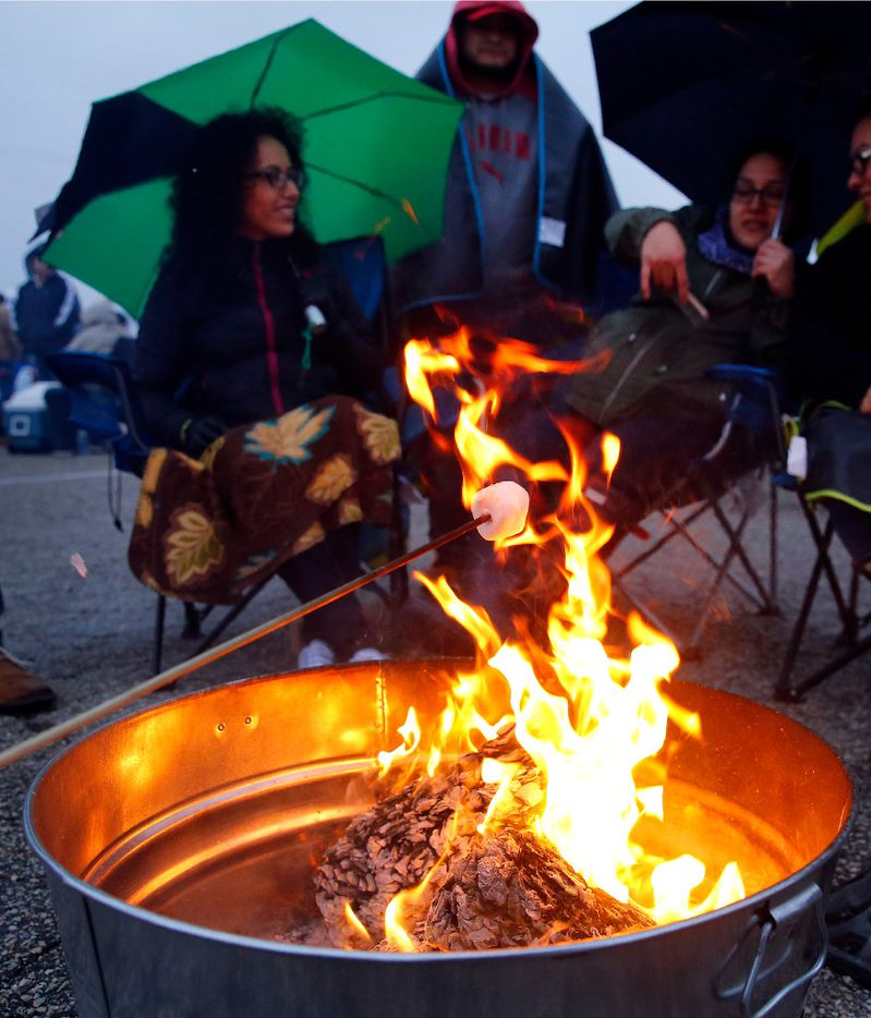 People makes Smores using a small fire before lighting paper lanterns and releasing them into the night sky during the Lantern Festival at Texas Motorplex in Ennis, Texas, Saturday, March 4, 2017. (Tom Fox/The Dallas Morning News)