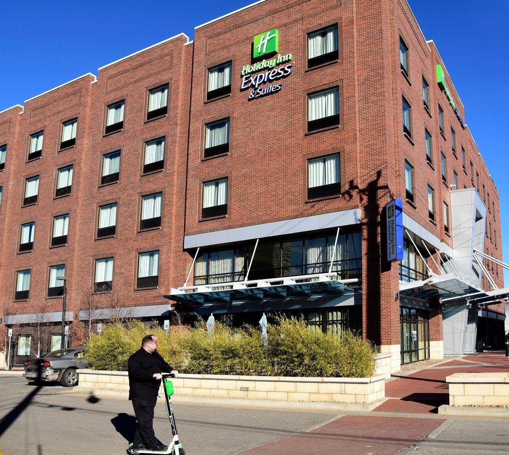 In this Jan. 7, 2019 photo, a man on a scooter rides past the Holiday Inn Express & Suites, in Bricktown, Okla.