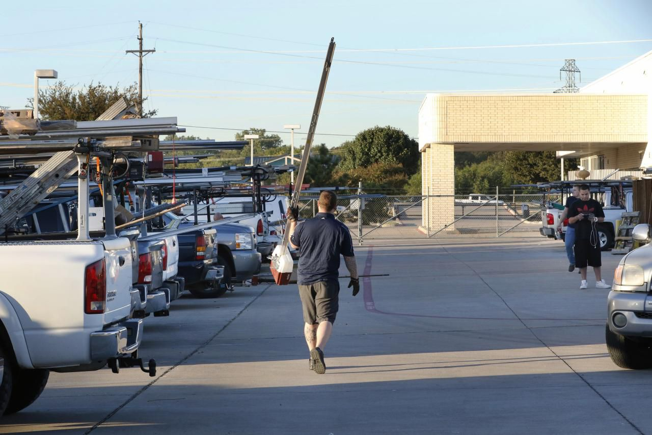 A Garage Door Services repairman carried a part through the company's parking lot in Carrollton on Wednesday.