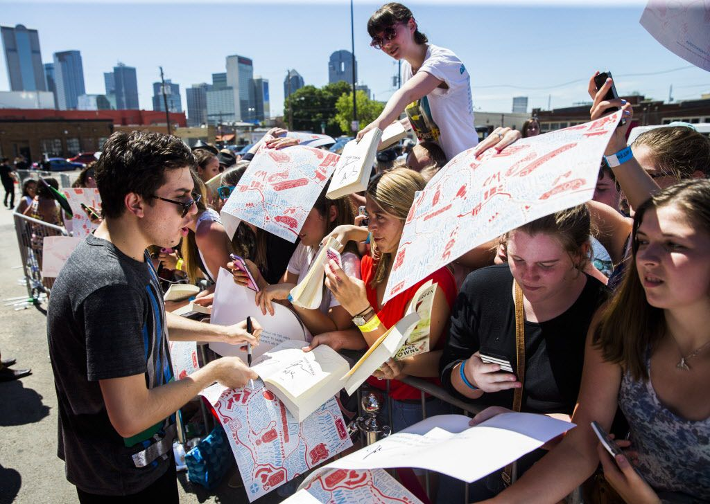 Actor Nat Wolff, left, signs autographs on the red carpet outside a promotional event for Paper Towns, a movie based on the book by John Green, on Thursday, July 16, 2015 at Bomb Factory in Dallas.  Wolff stars in the movie with Cara Delevingne.