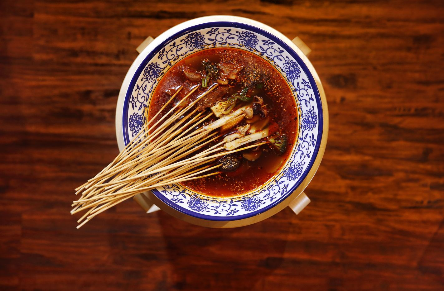 Skewered meats and seafood are served in a large bowl of spicy chicken broth with Sichuan pepper at Chuan Chuan Boiled Skewer Restaurant in Plano.  (Tom Fox/Staff Photographer)