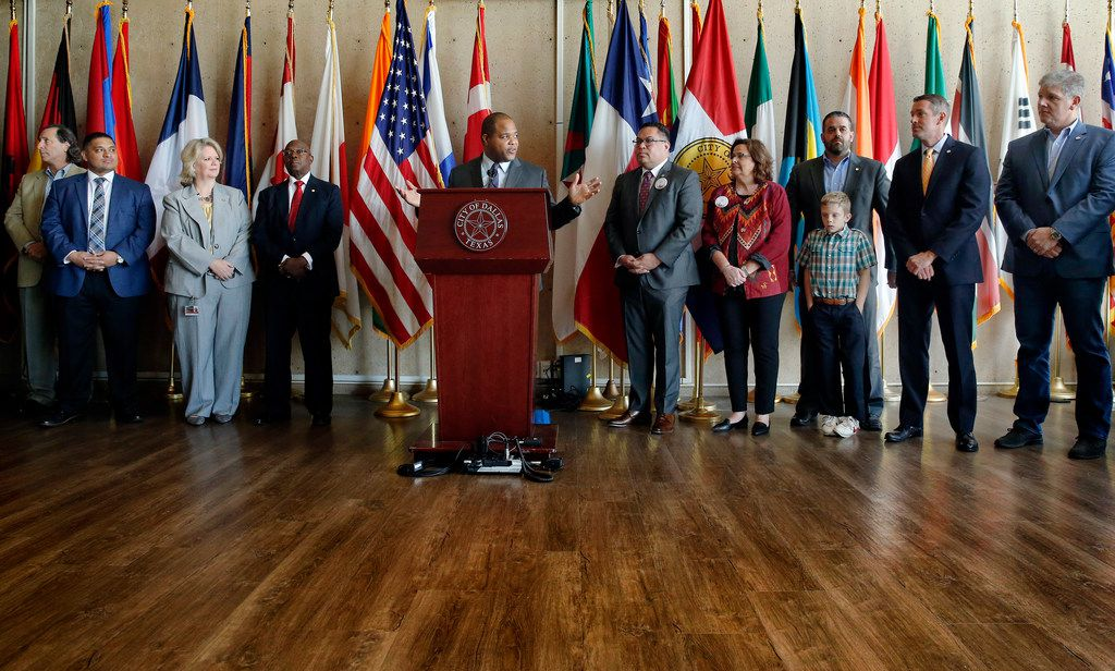 The Dallas City Council along with Mayor Eric Johnson (at podium) celebrated a unanimous vote on the budget, which largely focused on public safety and reduced the property tax rate by one-hundredth of a cent, at Dallas City Hall, Wednesday, Sept. 18, 2019.
