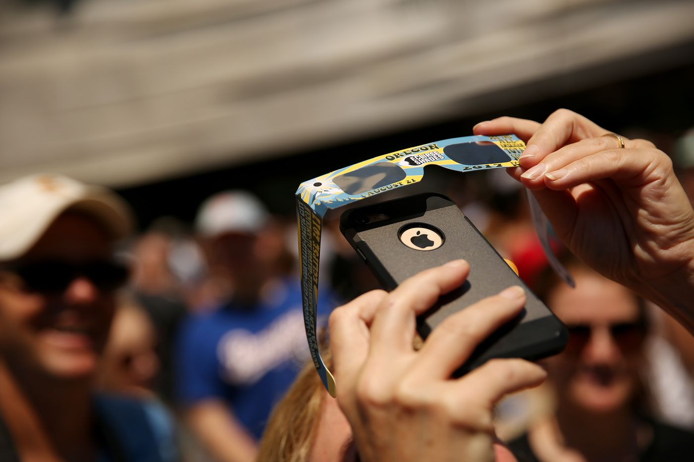 A person attempts to take a photograph of the sun through  pair of glasses during a solar eclipse outdoor watch party at the Perot Museum of Nature and Science.