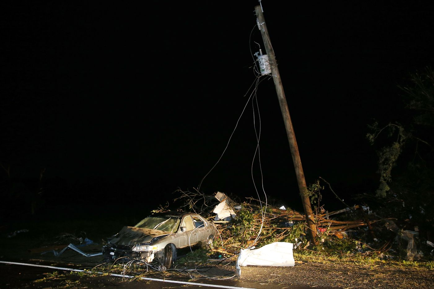 A car is part of the tornado debris field that was piled up State Highway 80 in Fruitvale, Texas.(Tom Fox/The Dallas Morning News)