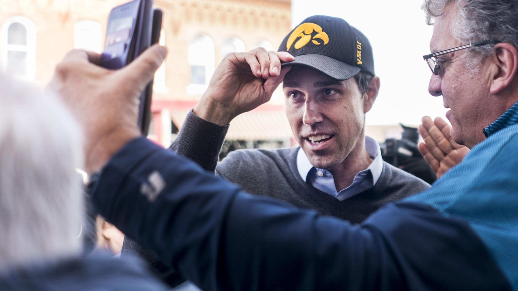 Newly announced 2020 Democratic presidential candidate Beto O'Rourke adjusts his new Iowa hat before meeting voters at the Sing-A-Long Bar and Grill in Mount Vernon, Iowa, on Friday, March 15, 2019.