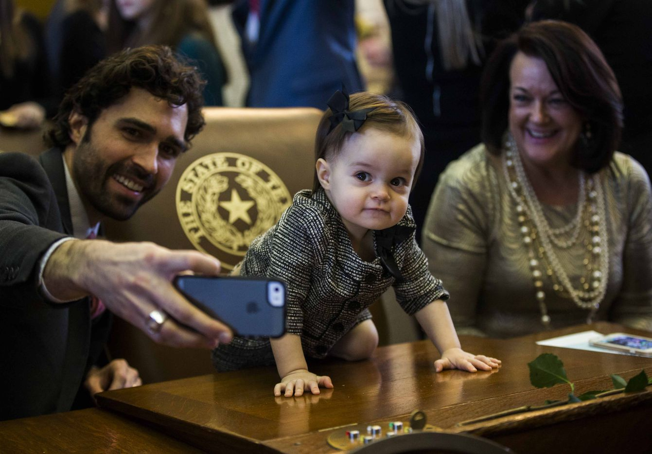 Brandon Zerwas (left) takes a photo of himself with Tinley Zerwas, 1, and Sylvia Zerwas during the first day of the 85th Texas Legislative Session on Tuesday at the Texas State Capitol in Austin. The three are family of state Rep. John Zerwas.