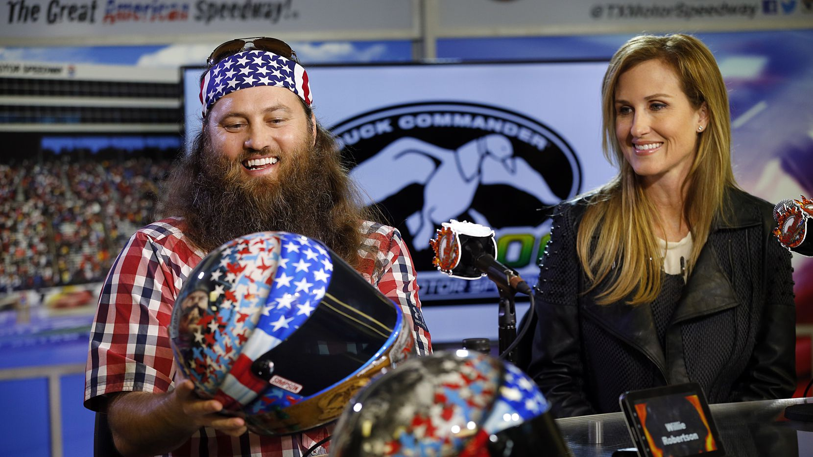 "Duck Commander/A&E's ""Duck Dynasty"" Willie Robertson admires the race helmet adorned with pictures of his family  with his wife Korie during Texas Motor Speedway's 'Big Hoss TV"" press preview in Fort Worth, Wednesday, March 19, 2014. The 94ft x 218ft screen on the backstretch of the track will be the largest HD video board in the world at  sporting venue.  Its built to withstand winds of 120 mph. Fans watched the latest episode of Duck Dynasty with actors from the show in attendance. (Tom Fox/The Dallas Morning News)"
