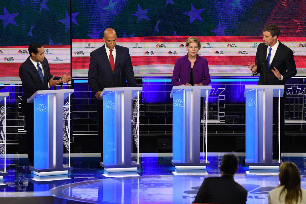 Former San Antonio Mayor Julian Castro, far left, and former El Paso Rep. Beto O'Rourke, far right, address each other at the first Democratic presidential debate as New Jersey Sen. Cory Booker and Massachusetts Sen. Elizabeth Warren look on. (Photo by JIM WATSON / AFP)JIM WATSON/AFP/Getty Images