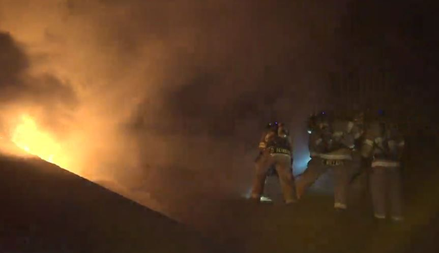 Fort Worth firefighters battle heavy smoke and flames as they try to chop through the roof of an apartment complex Wednesday morning.