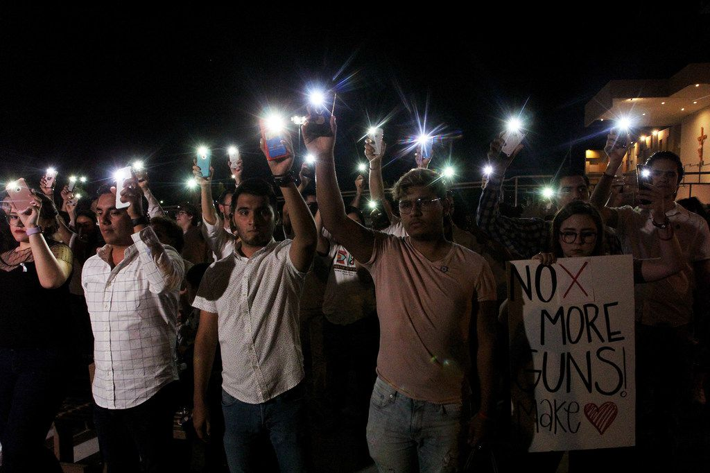 People held their mobile phones with flash on during a vigil in Ciudad Juarez, Chihuahua state, on Saturday, Aug. 3, 2019, after a mass shooting that left 20 people dead in El Paso.