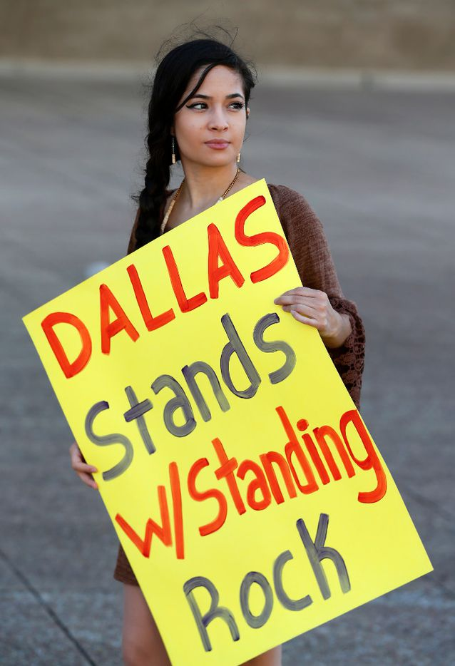 Environmental activist Victoria Guevara holds a sign to protest against construction of the Dakota Access Pipeline at Dallas City Hall in Dallas, Tuesday, Oct. 11, 2016.