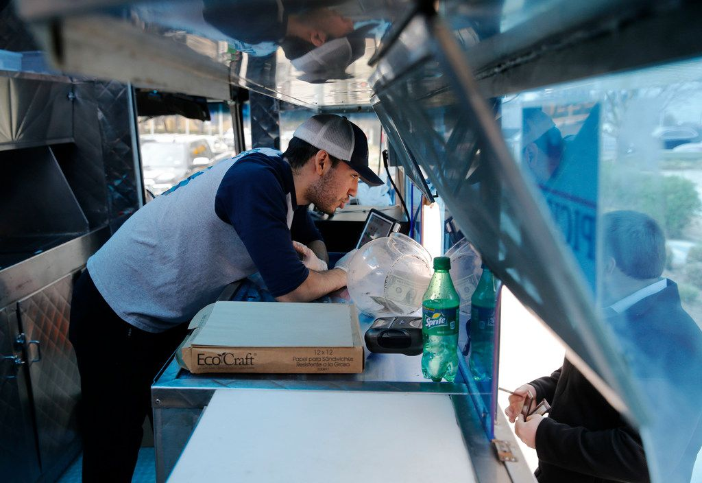 Cesar Villa of Frisco takes an order from a customer at Ruthie's Rolling Cafe food truck at Klyde Warren Park in Dallas on Wednesday, March 20, 2019. Chad Houser of Cafe Momentum is collaborating with Ashlee Kleinert of Ruthie's Rolling Cafe food truck to create a new opportunity for at-risk youth. Kids who work at Cafe Momentum can continue their apprenticeships by taking charge of a food truck.