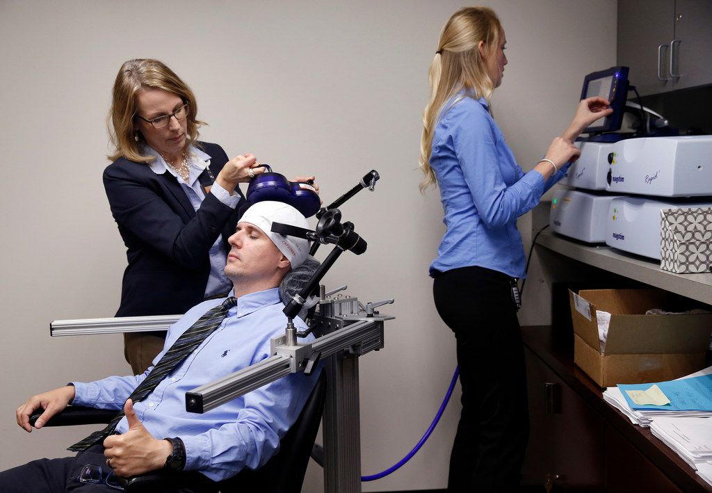 Lab manager Ellen Morris adjusts a rTMS (repetitive Transcranial Magnetic Stimulation) device on research assistant Justin Jacqmain as fellow assistant Rachel O'Hair reads them on the main unit at UT-Dallas' Brain and Behavioral Sciences Department in the hospital district of Dallas. Forty Veterans Administration hospitals have been using this procedure for years to treat depression and obsessive compulsive disorder.