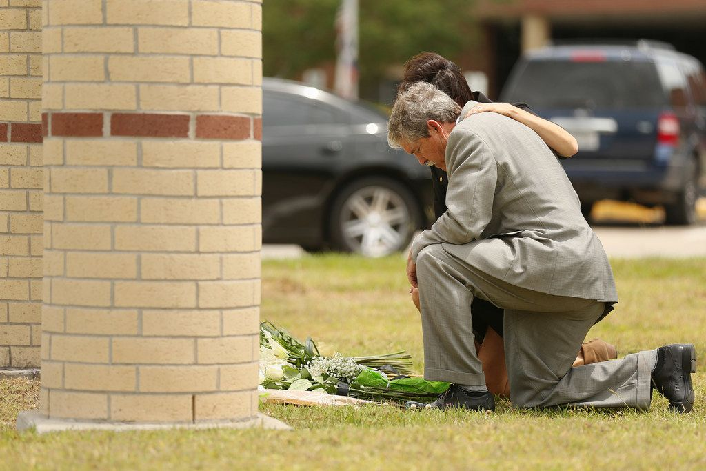 Texas state senator Larry Taylor, of district 11, and his wife Kerri Taylor have a silent moment at Santa Fe High School to lay flowers at the school in Santa Fe, Texas Sunday May 20, 2018. On Friday morning May 18, 10 people were killed and 13 were injured after a shooting at Santa Fe High School. (Andy Jacobsohn/The Dallas Morning News)