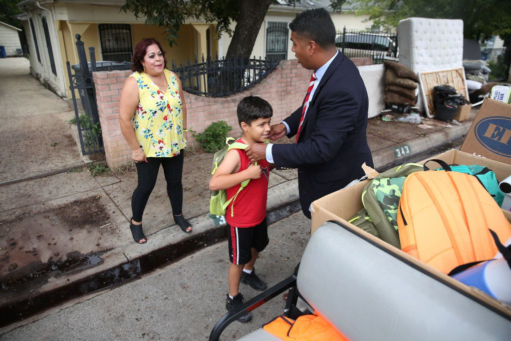 Adan Gonzalez, a new third-grade teacher at Bowie Elementary School, delivers a backpack to Willie Alcantara as he chats with his mother, Carmen Bueno. Bueno is one of the many Mexican immigrant mothers of students at Bowie Elementary.