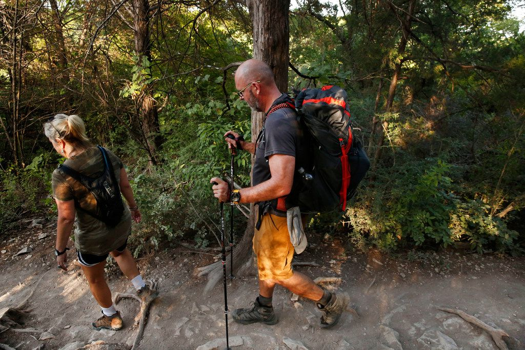 Heath Murry and his friend Julie Anderson hike Cattail Pond Trail at Cedar Ridge Preserve in Dallas on Friday, June 29, 2018. (Rose Baca/The Dallas Morning News)