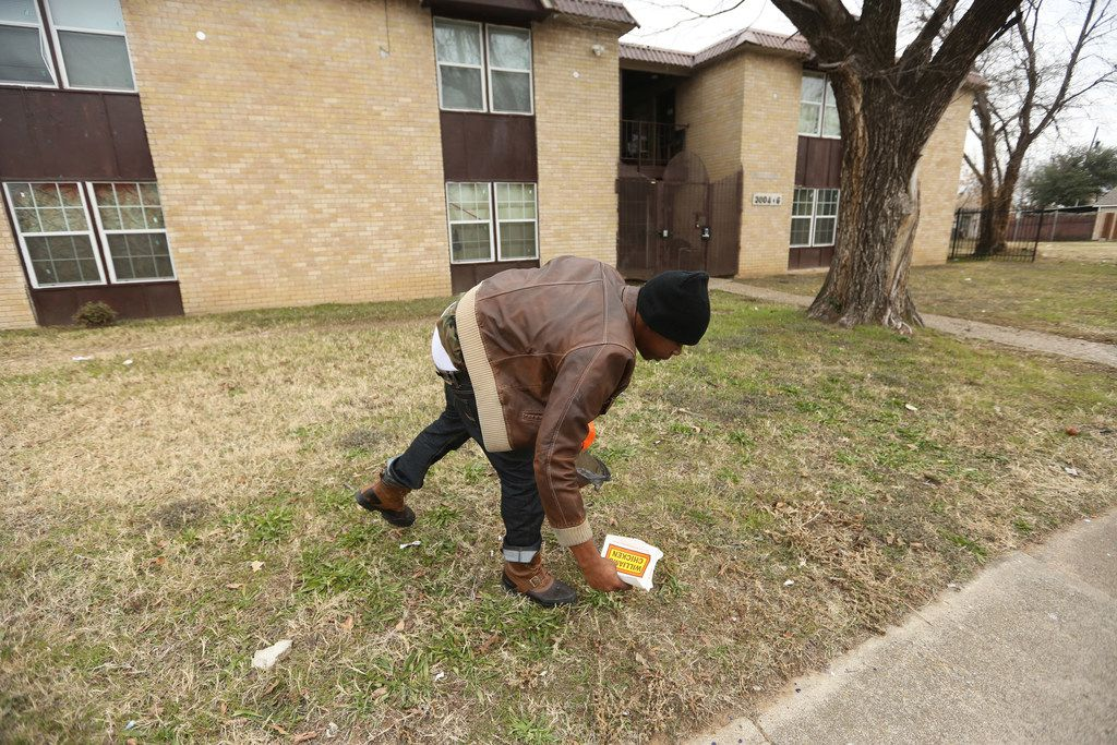 Dominique Lindsey, a resident of the 14-unit apartment complex located at 3006 Holmes St.  in South Dallas picks up trash Tuesday morning. He's been a resident since May.