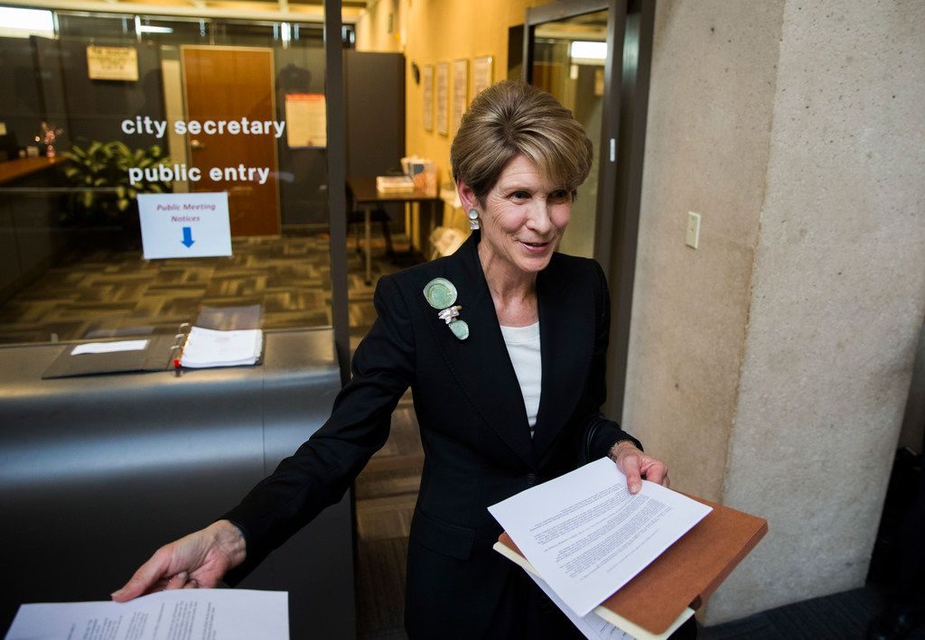 Former Dallas Mayor Laura Miller speaks to reporters as she leaves the city secretary's office after filing the required petition signatures to secure a place on the ballot for Dallas City Council District 13 at City Hall.